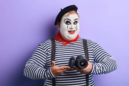 smiling pleasant mime with white face taking picture in the studio with blue wall. close up photo.