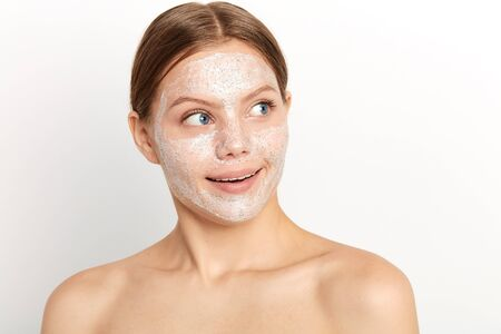 good looking young woman with cream on her face looking at copy space. place for text, advert. close up portrait