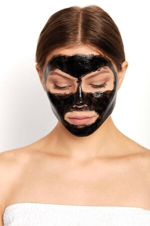 young woman with nourishing mask looking down. close up portrait, studio shot, high resolution Stockfoto
