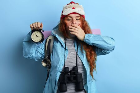 sleepy young hiker holding a clock, has problems to get up i the morning, tourist has slept badly. insomnia concept