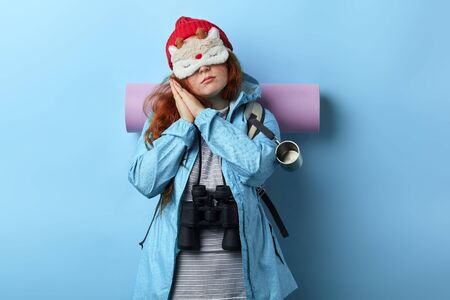 Young ginger girl sleeping mask on her face pretending sleeping .lifestyle, free time, spare time, isolated blue background, studio shot . tiredness Stok Fotoğraf