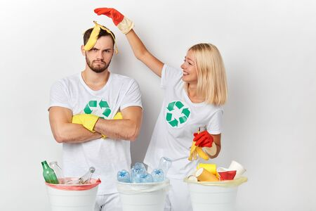 a young couple recycling plastic, glass,paper. serious unhappy man standing with crossed arms, while his girlfriend puting the banana peel on his head and laughing at him