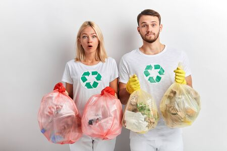 young people with bugged eyes holding rubbish and looking at the camera, isolated white background
