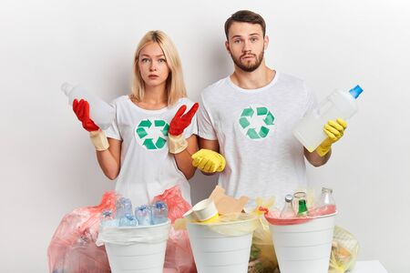 serious puzzled emotional couple doesnt know what to do with litter. Environmental pollution problem. Stop nature garbage environment protection. lifestyle. man and woman holding bottles