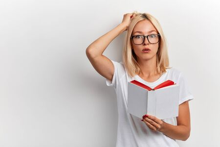 young puzzled serious blonde student cannot prepare for exams, young woman scartching her head, holding a book, isolated white background, studio shot, lifestyle, free time,spare time, copy space Stok Fotoğraf