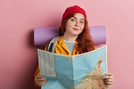 smiling positive ginger tourist holding a map, making decision where to travel, close up photo. isolated pink background, studio shot. people, hobby, interest