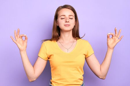 Front view of young beautiful female yoga instructor with peaceful face expression, doing breath exercises, meditates indoors with closed eyes, tries to relax and calm down. Stock fotó
