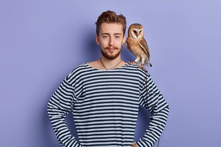 young man going to show tricks with an owl, isolated blue background, studio shot. clown having arest during working day