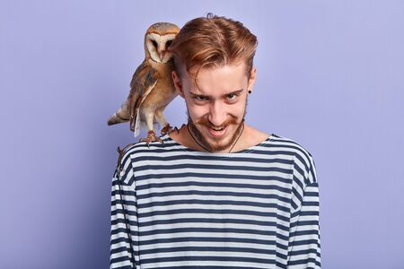 crazy angry guy frowning his eyebrows and looking at the camera, young man with an owl on his shoulder making face Imagens