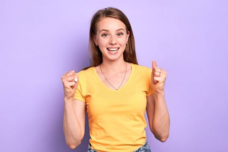 Cheerful graduated female teenager clenches fists, celebrates her admission to the university, showing success gesture, exclaims with excitement, feels extremely happy. Studio shot, purple background