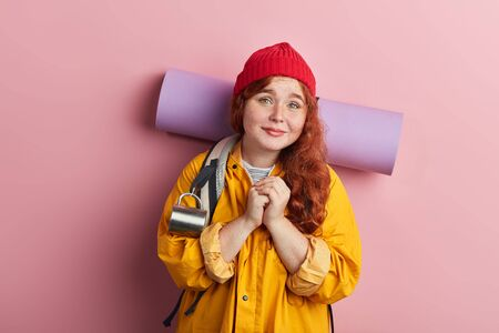 attractive plump female traveler asking the direction. can you help me. ginger girl with keeping palms together asking to stay overnight. isolated pink background 写真素材