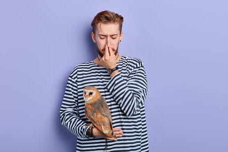 junger Mann, der eine Eule hält und sich die Nase kneift, um einen ekelhaften Geruch zu vermeiden. Nahaufnahme Foto. isolierter blauer Hintergrund, Studioaufnahme.
