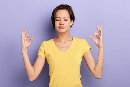 relaxed careless girl makes mudra sign, relaxes after hard working day, keeps eyes closed, practises yoga against violet background. Young pretty woman meditates in the studio . Relaxation concept Stock fotó