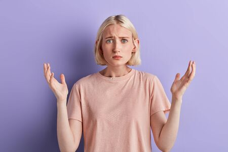 Surprised serious blonde young woman expresses puzzled emotion, she cannot understand what wrong is. what is the problem Stockfoto