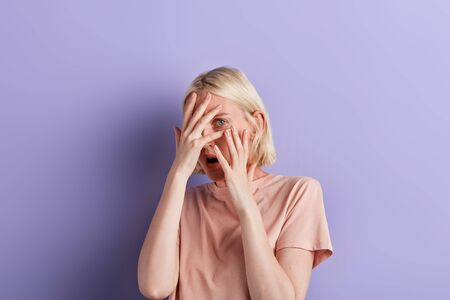 young scared woman covering her face with hands and spies, hiding her eyes behind palms.close up portrait, facial expression. studio shot. isolated violet background
