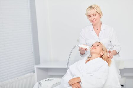 hardworking therapist lifting, cleansing the facial skin of patient at workplace. close up photo, copy space