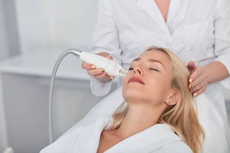 mujer agradable con los ojos cerrados recibiendo un tratamiento de belleza. Foto de cerca estilo de vida, ocio