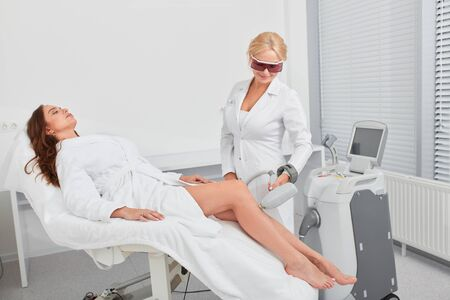 Laser epilation and cosmetology.blonde therapist in mask performing hair removal cosmetology procedure. close up photo. beauty, skin , legs care