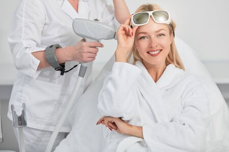 cheerful smiling blonde woman with glasses on her forehead preparing for laser skin procedures at beauty salon. Beauty Care. High Resolution. happiness