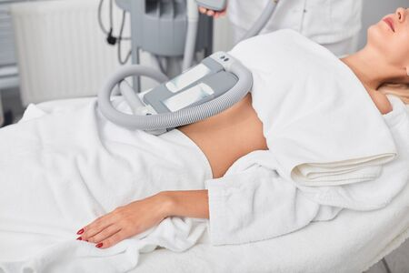 relaxed calm woman taking treatment in the clinic. close up cropped side view photo. machine for weight loss