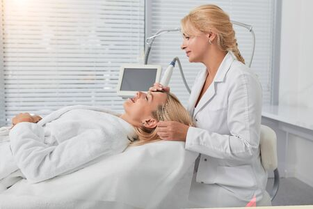 young doctor concentrated on cleaning womans face. close up side view photo