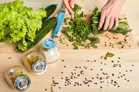 Cropped view of unrecognizable womans hands chopping scallions and making green salad with lettuce, cucumbers, parsley and different spices, cooking healthy diet food, using organic fresh products. Stockfoto