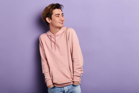 smiling cheerful man wearing pink hoodie, jeans looking aside, waiting for his friends. copy space. fashion, people, youth
