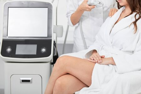 young woman in white robe with crossed legs sitting in the beauty salon and waiting for procedure. close up cropped portrait, studio shot.