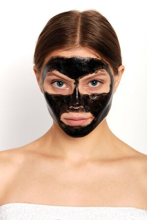 attractive girl has applied a black mask on her face, close up portrait, studio shot. isolated white background. studio shot