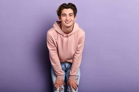Handsome young cheerful smiling man in pink fashion sweater, isolated on blue background.close up photo. people, lifestyle,copy space.