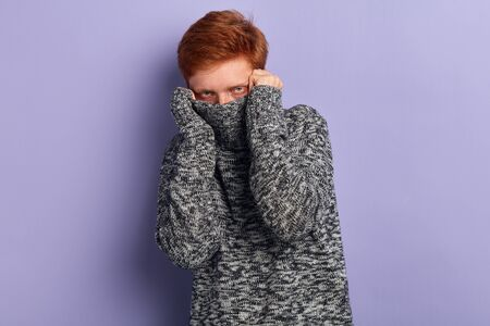 portrait of young sad unhappy scared guy hiding his face in sweater.close up photo. isolated blue background, studio shot. fobia, fear