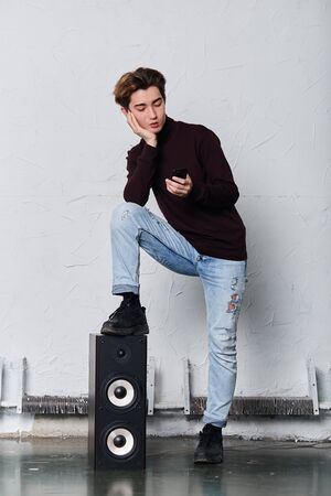 serious stylish man using his smart phone while standing in the music studio, free time, spare time, full length photo. gadget concept. addiction