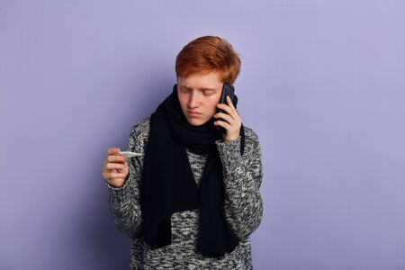 young unhappy sad man holding smart phone in hand and thermometer, making a phone call. Cold and Sickness. health crea, lifestyle. isolated blue background, studio shot