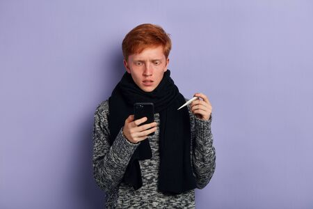 unhappy young man wearing sweater and black scarf browsing the internet, looking for effective treatmnt, folk medicine. close up photo. isolated blue background, studio shot