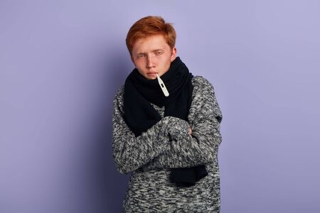 weak young man wearing fashion sweater and scarf standing with crossed arms isolated over blue background, studio shot 스톡 콘텐츠