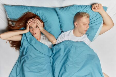 sick young woman has headache at night, health problem. close up top view photo. depression. ginger girl touching her head. Banque d'images - 129669173