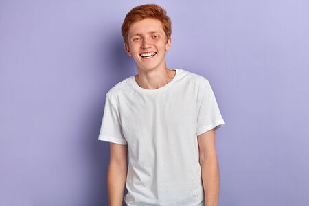 Portrait of young happy attractive man , wearing a white t-shirt, smiling and looking at the camera isolated over blue background.people, lifestyle Stok Fotoğraf