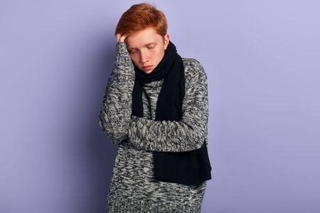 young man in warm sweater has a headache, guy suffers from desease. close up portrait, studio shot