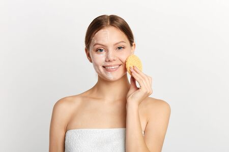 young cheerful girl wearing towel on nude body wiping cream with sponge, close up portrait, free time, spare time, healthy lifestyle, studio shot