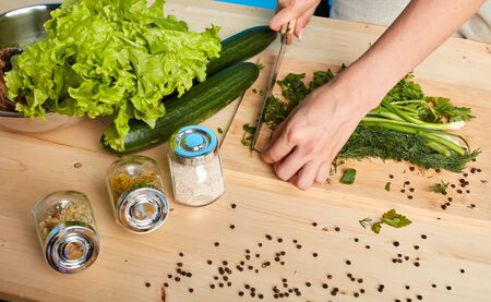 High angle view of womans hands cutting different green vegetables on wooden board, fresh cucumbers, scallions, parsley and spices on the table, cooking healthy lunch. Cropped view, studio shot. Stock Photo