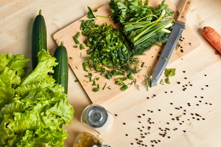 Close up high angle view of green lush vegetables on wooden table, fresh cucumbers, lettuce, scallion and parsley, pepper and species. Healthy organic vegetarian food concept.