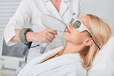 relaxed young blonde client receiving hair removal laser epilation. close up side view photo