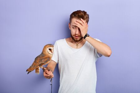 serious unhappy zoo keeper suffer from headache, close up portrait, isolated blue background, studio shot,