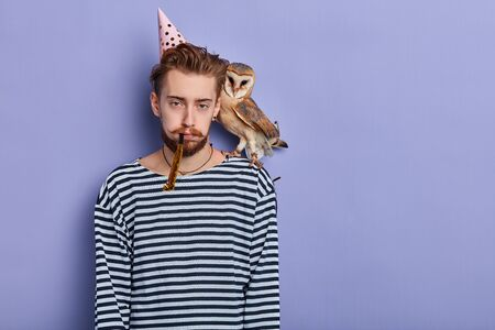 Unhappy young man with an owl in his shoulder is disappointed because nobody came to celebrate his anniversary, . People and celebration. isolated blue background