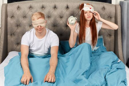 tired depressed young man and woman in sleeping mask hate alarm clock. they dont want to go to work. laziness concept