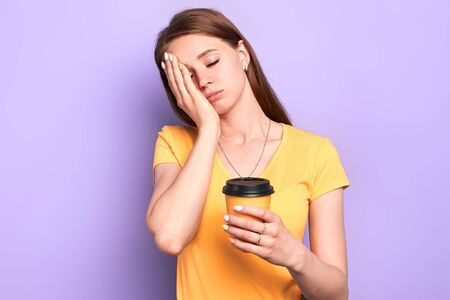 Studio shot of sleepy female student holding paper cup of coffee to go, standing with closed eyes, with one hand on her face, extremely tired after sleepless night, prepared to difficult exam.