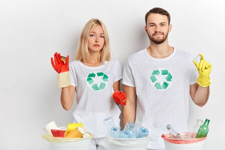 young attractive man and woman collecting used batteries. close up portrait, isolated white background, environmental program concept. recycling activity