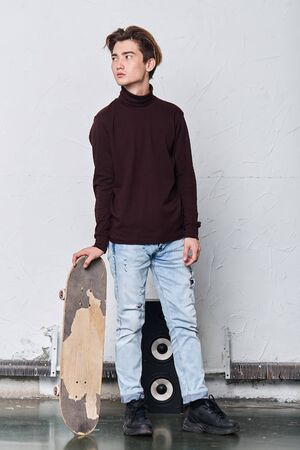 good looking serious street guy standing near his skateboard looking aside having a rest after riding, full length photo.