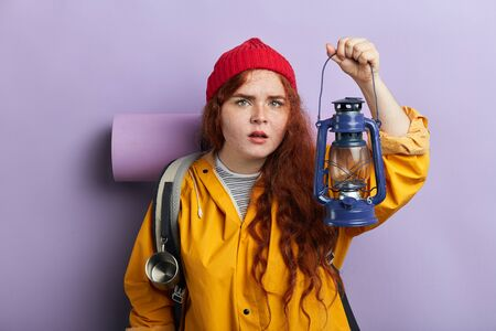 emotional fightened adventurer in red knitted cap, yellow jacket, cannot believe in eyes. close up photo. isolated blue background, studio shot, girl looking for a way from difficult situation