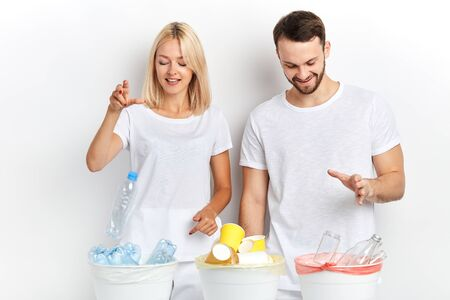 young cheerful happy woman and man separate waste and recycling it at workplace, good habit